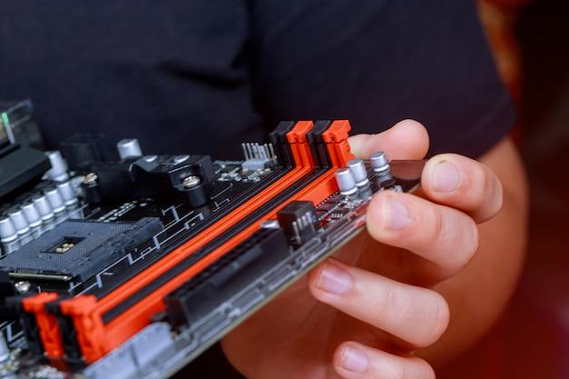 El ingeniero de instalación de memoria ram en la placa base del ordenador en el laboratorio de computación.