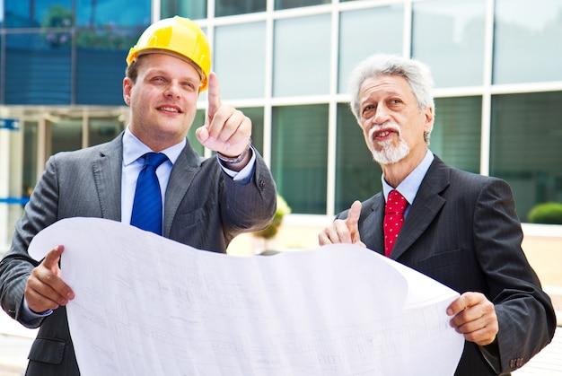 Ingeniero joven mostrando algo a su compañero en la obra.