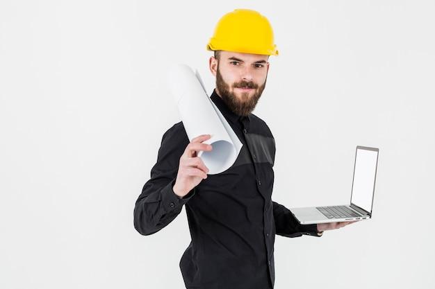 Un ingeniero joven que sostiene el modelo enrollado y la computadora portátil abierta contra el contexto blanco