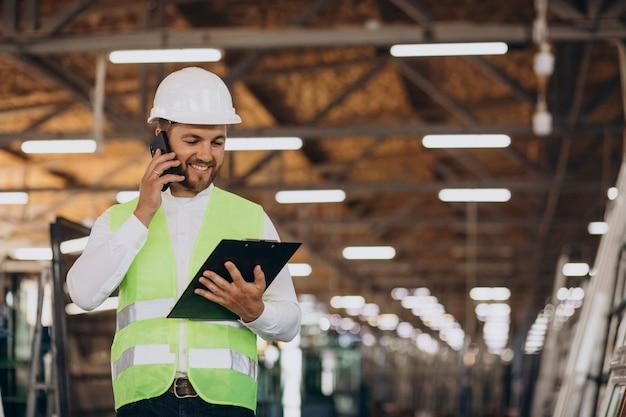 Ingeniero joven que trabaja en la fabricación de pedidos de fábrica en el teléfono