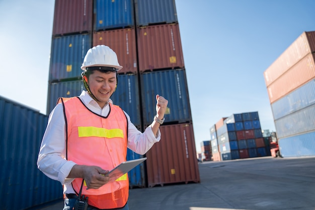 Ingeniero logístico de control en el puerto, cargando contenedores para camiones de exportación e importación logística