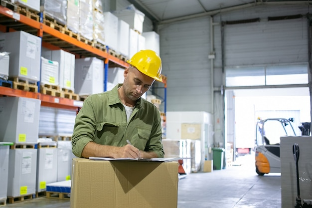 Ingeniero logístico masculino serio en casco y posición general en la pila de cajas y completando documentos. copie el espacio. concepto de cuello azul o trabajo