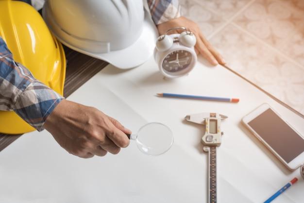 Ingeniero con lupa de vidrio para buscar papel en blanco para el nuevo proyecto