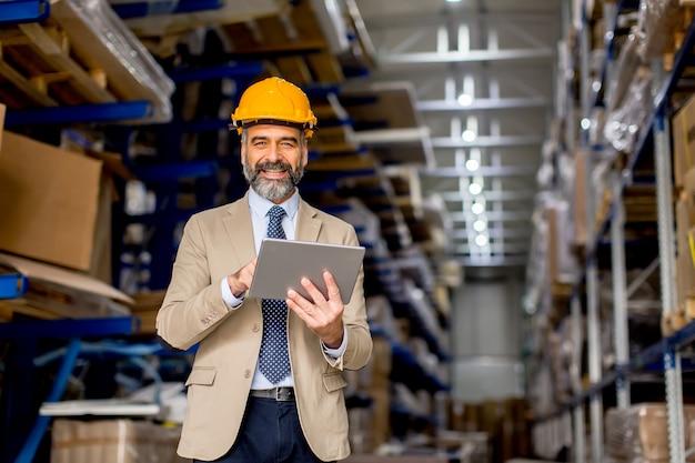 Ingeniero maduro guapo en el almacén con tableta digital