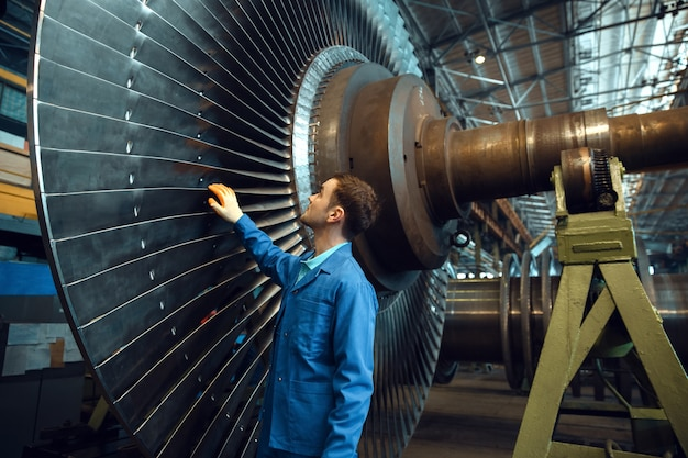 Ingeniero masculino comprueba las paletas del impulsor de la turbina en la fábrica.