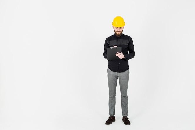 Ingeniero masculino escribiendo en portapapeles sobre fondo blanco