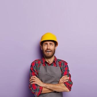 El ingeniero masculino insatisfecho estresante mantiene los brazos cruzados tiene una expresión facial miserable, usa camisa a cuadros y delantal, se enfoca arriba, recibe muchas tareas del jefe cansado del trabajo manual aislado en púrpura