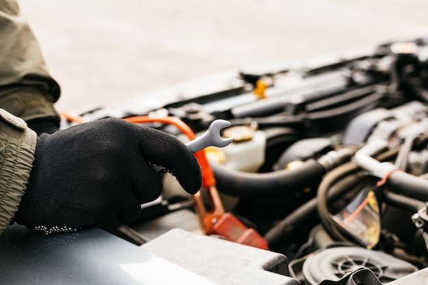 Ingeniero mecánico de automóviles con una llave en el proceso de fijación de un automóvil