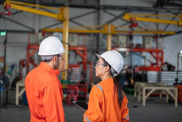 Ingeniero mecánico y femenino hablando en fábrica