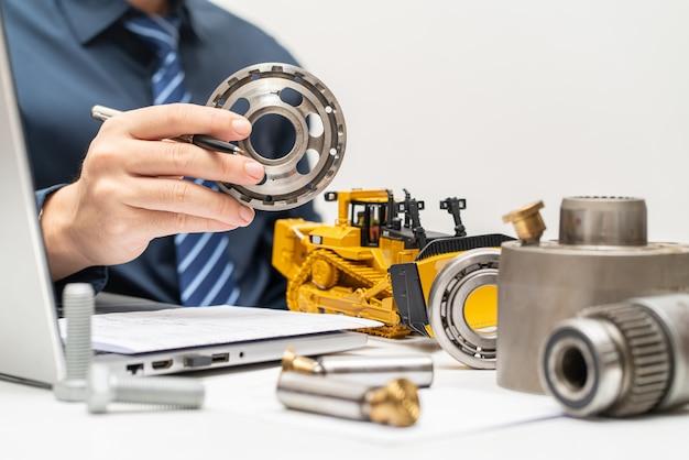Ingeniero mecánico profesional que inspecciona la placa de la válvula de la bomba de pistón hidráulico y redacta informes durante el día de trabajo en la oficina, el concepto de reparación de maquinaria pesada de mantenimiento