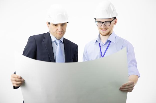 Ingeniero de minas y arquitecto trabajando, midiendo el diseño del plano del edificio