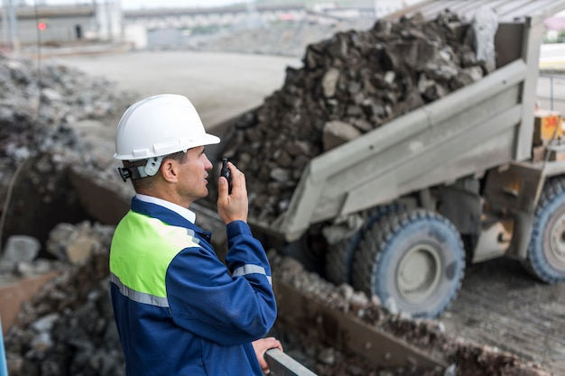 Ingeniero de minas en uniforme supervisa la descarga de dumpers