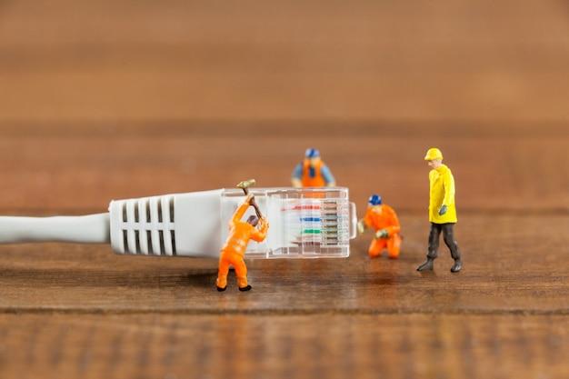 Ingeniero en miniatura y los trabajadores que utilizan cable lan