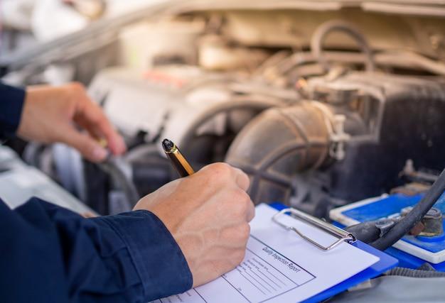 El ingeniero de motores está revisando y reparando el automóvil. servicios de atención fuera del sitio