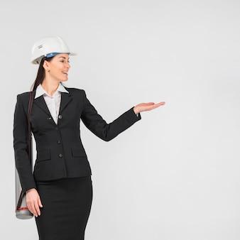 Ingeniero de la mujer en el casco que muestra con la mano
