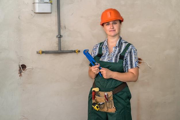 Ingeniero mujer con cinturón de herramientas y llave ajustable