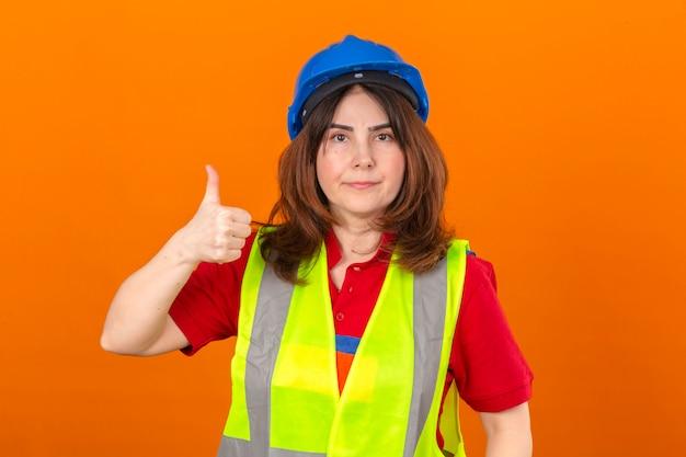 Ingeniero de mujer con gafas de chaleco de construcción y casco de seguridad con una sonrisa segura mostrando el pulgar hacia arriba de pie sobre la pared naranja aislada