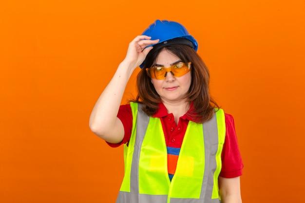 Ingeniero mujer con gafas de chaleco de construcción y casco de seguridad tocando el casco con la mano como gesto de saludo sobre pared naranja aislada