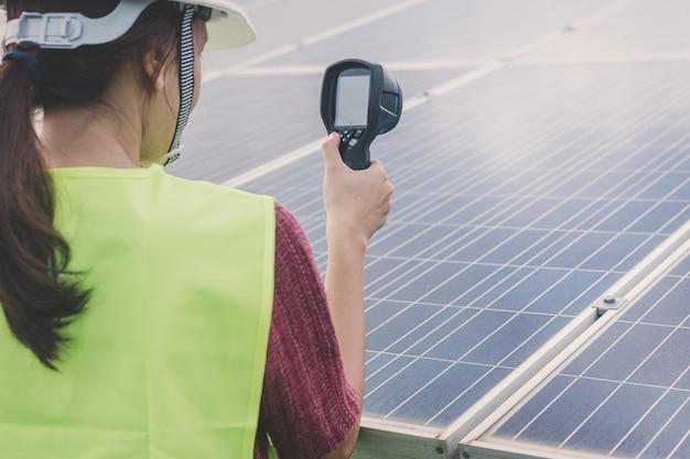 Ingeniero de la mujer usando una cámara termográfica para verificar la temperatura del calor del panel solar