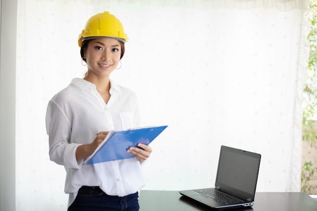 Ingeniero de mujeres asiáticas inspeccionando y trabajando y sosteniendo planos en la oficina