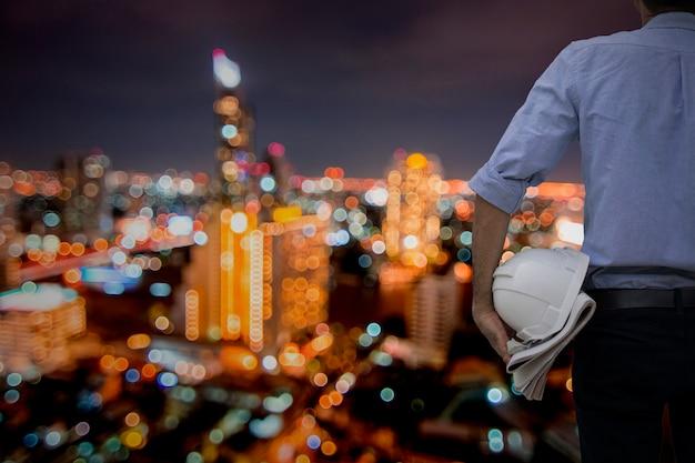Ingeniero o arquitecto de pie y sosteniendo casco y plano en la ciudad de noche