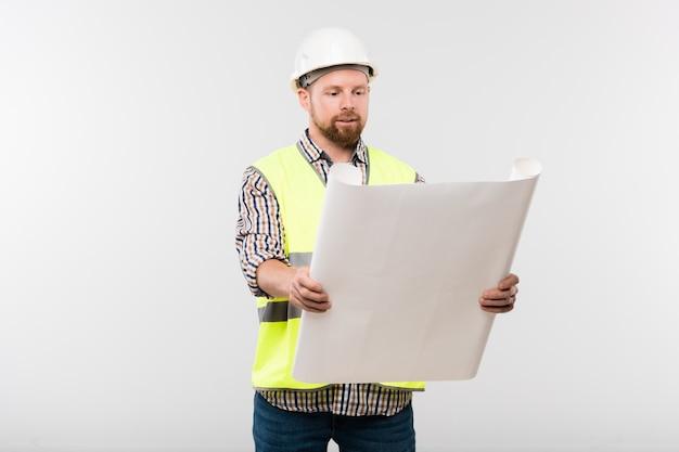Ingeniero o capataz exitoso en casco protector y ropa de trabajo sosteniendo el plano frente a sí mismo mientras mira el boceto