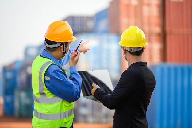 Ingeniero o capataz hable con un empresario asiático sobre la carga de contenedores desde un buque de carga.