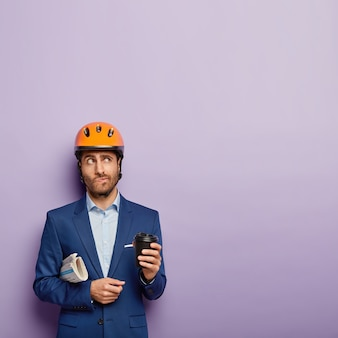 Ingeniero pensativo bebe café para llevar, tiene descanso, usa casco protector