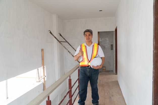 Ingeniero profesional asiático trabajando en la construcción de la casa para inspección