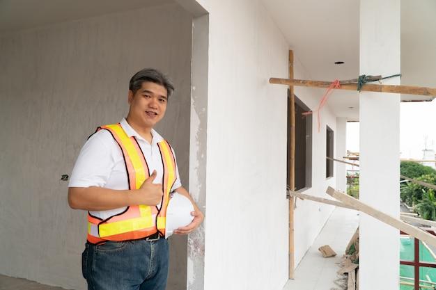 Ingeniero profesional asiático trabajando en el sitio de construcción de la casa para la inspección de la cabaña