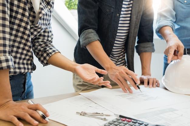 Ingeniero que discute la reunión que trabaja en el proyecto del modelo arquitectónico en el emplazamiento de la obra.