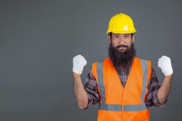 Un ingeniero que llevaba un casco amarillo con guantes blancos mostró un gesto en un gris.