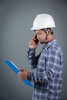 Ingeniero que sostiene modelos y que lee notas en el tablero mientras que se coloca en fondo gris.