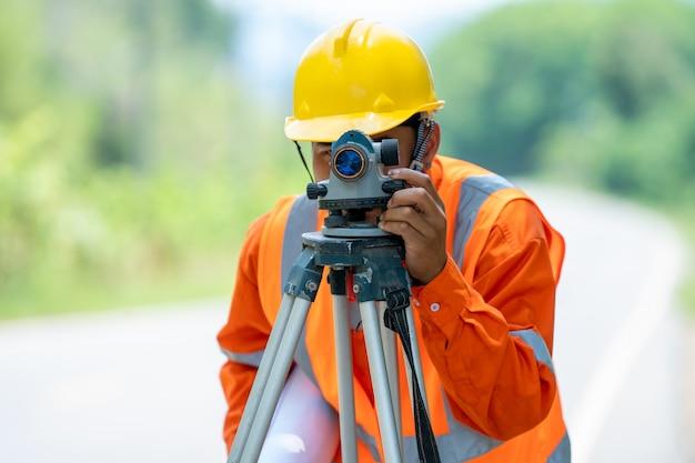 Ingeniero que trabaja con equipo de tránsito de teodolito en la carretera.