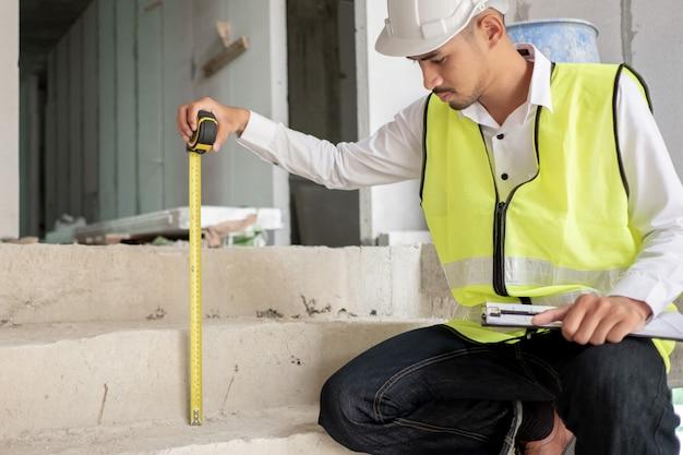 El ingeniero que verifica el defecto en el sitio de construcción mide la dimensión de la altura de la escalera