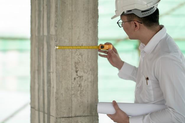 Ingeniero que verifica el defecto en el sitio de construcción mide la dimensión de la ventana en el panel de pared