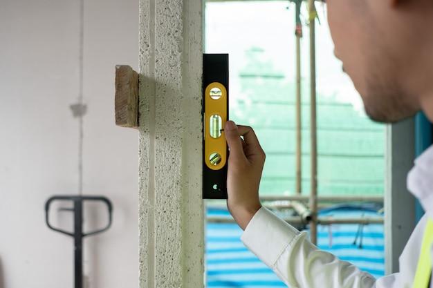El ingeniero que verifica el defecto en el sitio de construcción mide la dimensión de la ventana en el panel de pared