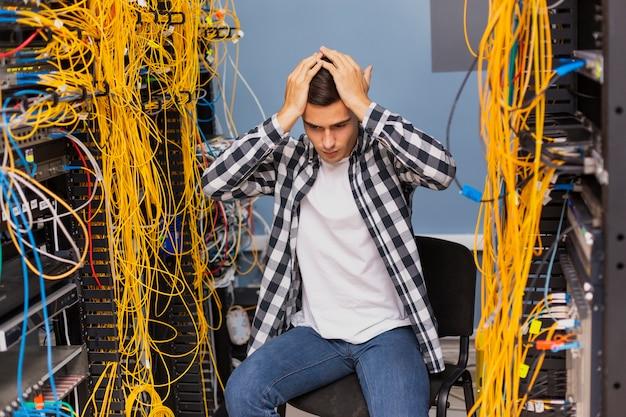 Ingeniero de red ansioso sentado en la sala de servidores