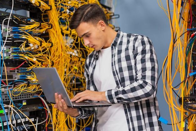 Ingeniero de redes con una laptop de tiro medio