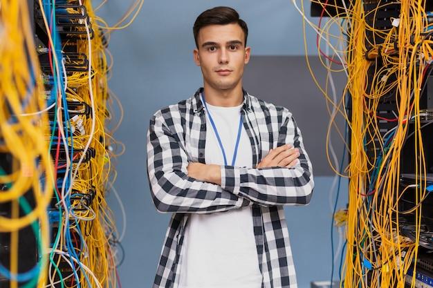 Ingeniero de redes de pie en la sala de servidores de tiro medio