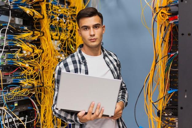 Ingeniero de redes en sala de servidores, plano medio