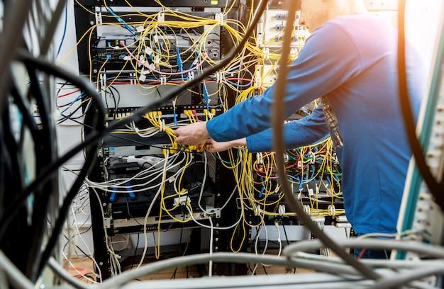 Ingeniero de redes trabajando en sala de servidores. conexión de cables de red a conmutadores