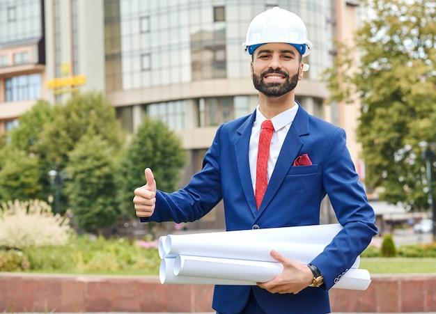 Ingeniero saudita sonriendo alegremente sosteniendo sus planos mostrando pulgares arriba copyspace