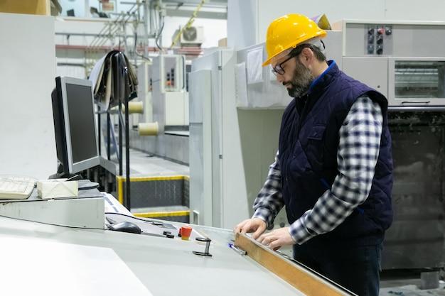 Ingeniero serio en vidrios que opera la máquina
