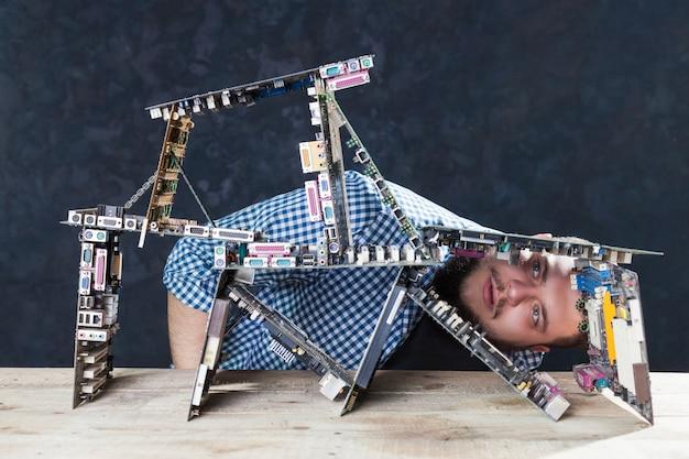 El ingeniero de servicio construye un castillo de naipes a partir de placas base. reparador hace diagnóstico de componentes electrónicos