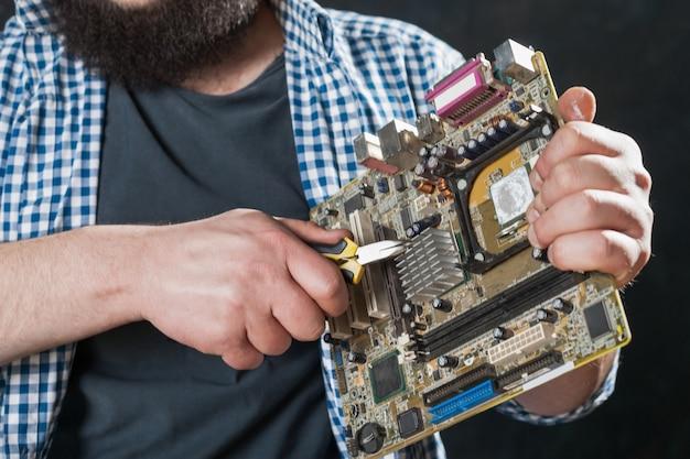 Ingeniero de servicio repara la placa base de la pc. reparador hace diagnóstico de componentes electrónicos