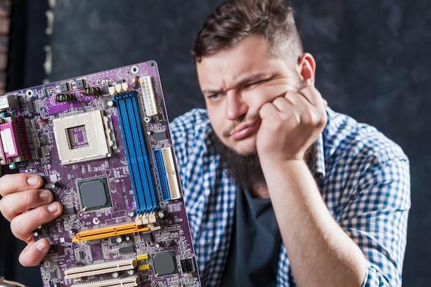 Ingeniero de servicio solucionando problemas con la placa base de la computadora. reparador hace diagnóstico de componentes electrónicos