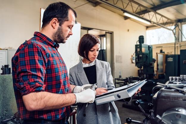 Ingeniero de sexo femenino que consulta con el operador de la máquina del torno usando el calibrador
