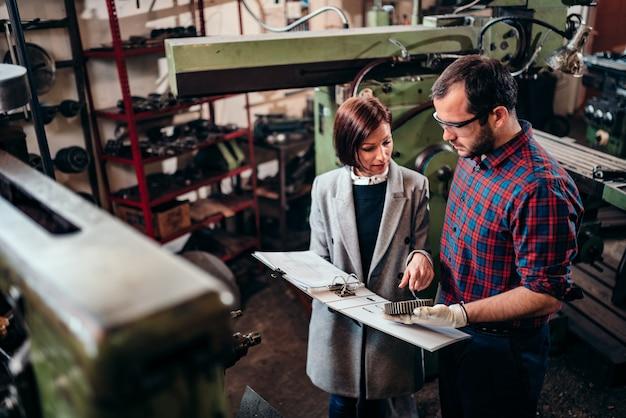 Ingeniero de sexo femenino que discute con el maquinista que sostiene la rueda dentada y que analiza el modelo