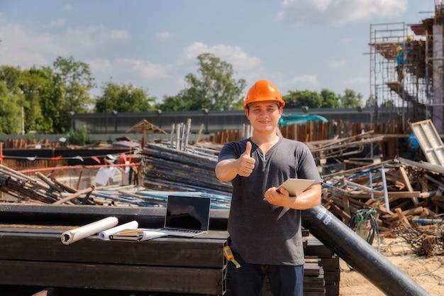 Ingeniero de sexo masculino con los brazos cruzados de pie en un sitio de construcción con una mirada feliz.